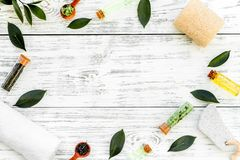 Tea tree spa composition. Fresh tea tree leaves, natural cosmetics, towel on white wooden background top view space for. Tea tree spa composition. Fresh tea tree stock photos