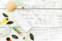 Tea tree spa composition. Fresh tea tree leaves, natural cosmetics, towel on white wooden background top view space for royalty free stock images
