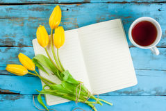 Tea, tulips and notebook on blue table Royalty Free Stock Images
