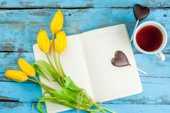 Tea, tulips and notebook on blue table Stock Images
