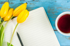 Tea, tulips and notebook on blue table Royalty Free Stock Photography