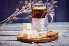 Tea with turkish delight. Hot fresh tea with turkish delight and small dry flowers in studio Stock Images