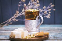 Tea with turkish delight. Hot fresh tea with turkish delight and small dry flowers in studio Royalty Free Stock Photos