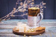 Tea with turkish delight. Hot fresh tea with turkish delight and small dry flowers in studio Royalty Free Stock Image