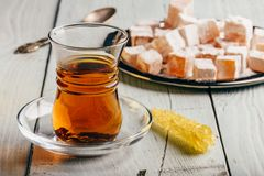 Tea with turkish delight Rahat Lokum. Tea in arabic glass with turkish delight Rahat Lokum over wooden surface stock photography