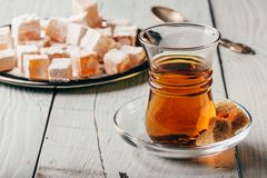Tea with turkish delight Rahat Lokum. Tea in arabic glass with turkish delight Rahat Lokum over wooden surface royalty free stock photo