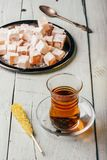 Tea with turkish delight Rahat Lokum. Tea in arabic glass with turkish delight Rahat Lokum over wooden surface royalty free stock photography