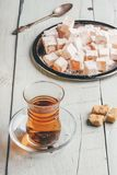 Tea with turkish delight Rahat Lokum. Tea in arabic glass with turkish delight Rahat Lokum over wooden surface royalty free stock images