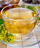 Tea from tutsan in glass cup with teapot Royalty Free Stock Image