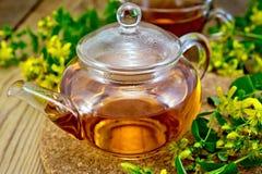 Tea from tutsan in glass teapot on board Stock Images