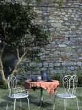 Tea for two. A rendered 3d design of a table and two chairs in a garden beside a tree and wall Royalty Free Stock Photography