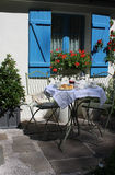 Tea For two. Garden table and chairs set up outside a sunny country cottage with tea and scones laid out on the table top. Set on a slate patio area. Evocative Royalty Free Stock Image