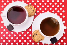 Tea for two. Close-up shot of two cups of tea with chocolate chip cookies placed on a plateau Stock Photos
