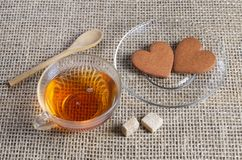 Tea and two ginger heart-shaped cookies stock photos
