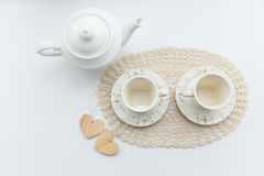 Tea for two. Two white cups of tea with two hearts and kettle. Tea for two. Two white cups of tea with two hearts and kettle royalty free stock image