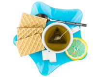 Tea with wafers, sugar and lemon in blue plate Royalty Free Stock Images