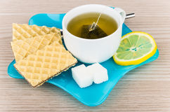 Tea with wafers, sugar and lemon in blue plate Stock Photo