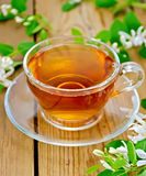 Tea with white flowers of honeysuckle on board Stock Images
