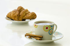 Tea in white mug with cinnamon and croissant on white plate. On white backgound Royalty Free Stock Images