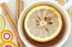 Tea in white mug with slice of lemon and cinnamon. On white background Stock Photography