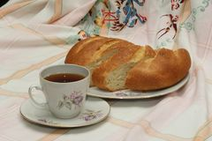 A cup of tea and bread cutted. Tea in white porcelain cup with grey and violet ornament  and bread cutted on white plate on coloured tablecloth Royalty Free Stock Images
