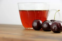 Tea – wild cherry. Hot tea wild cherries in a glass with some fresh wild cherries in front, standing on a wooden board Stock Photo