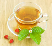 Tea and wild strawberries Stock Images
