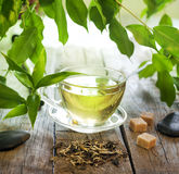 Tea on wooden boards with green leaves Royalty Free Stock Photo