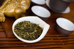 Tea leaves in cup on wooden table. Chinese tea in white cup Royalty Free Stock Photo
