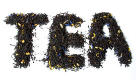 TEA word made of earl grey black tea. Iisolated on white background Royalty Free Stock Images