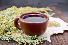 Tea with wormwood in clay cup on board. Herbal tea in a brown clay cup, twigs gray sagebrush, wormwood dried on a paper on the background of a wooden tabletop Royalty Free Stock Photography