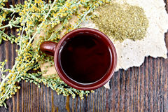 Tea with wormwood in clay cup on board top. Herbal tea in a brown clay cup, twigs gray sagebrush, wormwood dried on a paper on the background of wooden boards on Stock Photography