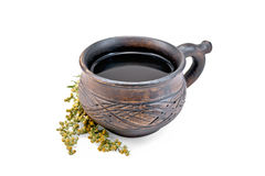 Tea with wormwood in clay cup. Herbal tea in a brown clay cup, twigs gray wormwood with a light shade on white background Stock Images