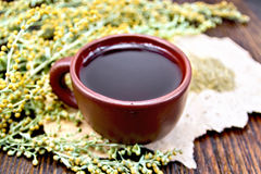 Tea with wormwood in clay cup on paper Stock Photos