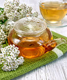 Tea with yarrow in glass teapot on board. Yarrow tea in a glass teapot on a green napkin, fresh yarrow flowers on a background of light board royalty free stock photography