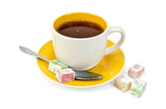 Tea in yellow cup with lokum Royalty Free Stock Photo