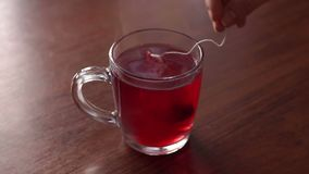 Teabag in the cup with hot water. Close-up of a glass mug with hot water and a bag of floral red tea, slow motion. A girl is brewing a bag of tea in a mug on a stock video footage