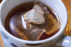 Teabag and infusing in mug of boiling water Royalty Free Stock Photography