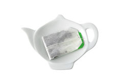 Teabag on teapot shaped saucer Stock Image