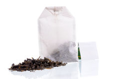 Teabag with white label and tea loose. Heap of tea loose and teabag with white label. Focus on teabag Royalty Free Stock Images