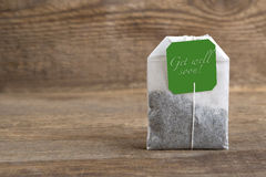 Teabag on wooden background, get well soon. Closeup of green teabag on wooden background, get well soon stock photo