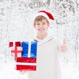 Teaboy con el sombrero de santa y las cajas de regalo rojas que muestran los pulgares para arriba Foto de archivo
