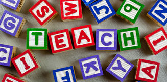 Teach. Wooden blocks forming the word TEACH in the center stock photography