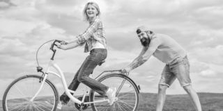 Teach adult to ride bike. Find balance. Woman rides bicycle sky background. How to learn to ride bike as an adult. Girl. Cycling while boyfriend support her royalty free stock photography