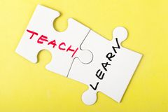 Teach and learn. Words written on two pieces of puzzle stock images