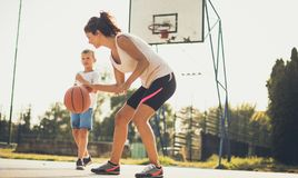 Teach them that sport is important. Mother and son playing basketball royalty free stock image
