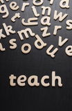 Teach in Wooden Letters. Wooden letters spell the word Teach on a blackboard royalty free stock image