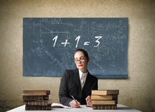 Teacher. Portrait of a teacher sitting in front of a blackboard with a wrong addition written on it royalty free stock image