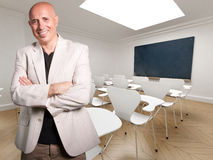 The Teacher. Mature teacher happily smiling in an empty classroom royalty free stock photo