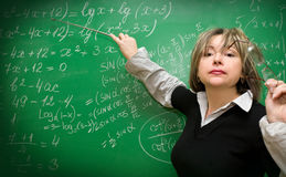 Teacher. Shows the formula on the green chalkboard Royalty Free Stock Images